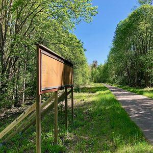 En skylt som står bredvid en gammal väg med träd och grönska runt omkring.
