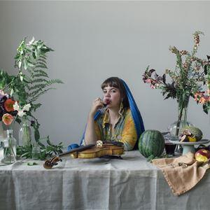 Frida Edlund, Dam sitter vid bord med fiol.