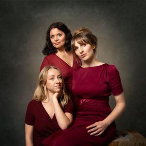 Tre damer i röda klänningar.