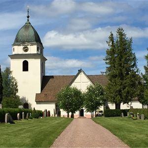 Rättviks kyrka sett från sidan med gröna gräsmattor.