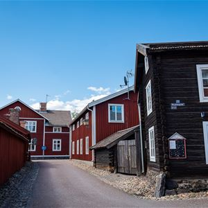 Röd gammal träbebyggelse i stadsmiljö.