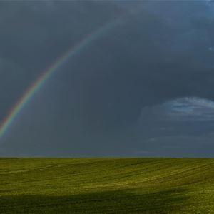 En liten regnbåge som sträcker sig över en mörk himmel.