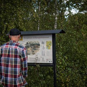 En man i rutig skjorta och keps står och tittar på en informationstavla, omgiven av lövskog.