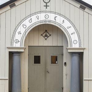 Vit byggnad med symbolen för koppar och andra tecken.