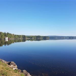 Vy över sjön Varpan, spegelblankt vatten vit byggnad skymtar i bakgrunden av bilden.
