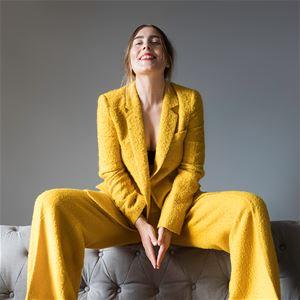 Miss Li sitter på en soffa i gula kläder.