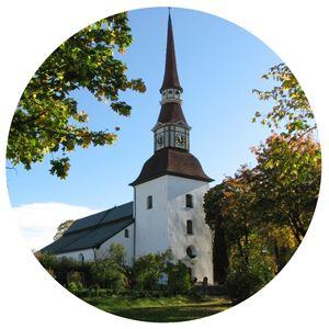 Yvonne Eriksson,  © Yvonne Eriksson, En vit stor kyrka med träd och buskar runt om.