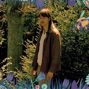 Artist som står med blommor omkring sig.