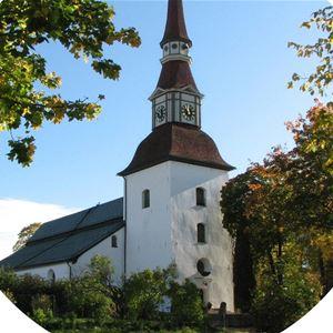 Yvonne Eriksson,  © Yvonne Eriksson, En stor gammal vit kyrka med buskar och träd runt omkring.