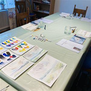 © Cristina Pérez-Selkman, Ett bord med akvarellmålningar och material.