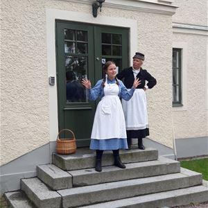 © Eva Ersbacken, Hedemora kommun, En flicka i blå klänning och vitt förkläde står på en trappa tillsammans med en kvinna i svart hatt, svart klänning och vitt förkläde.
