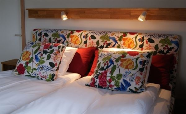 headboard and pillows in floral, colorful textile.