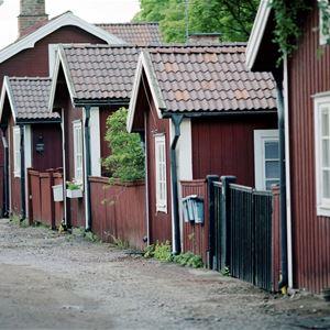 Röda gamla trähus på rad längs en gata.