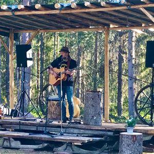 © Victoria Johansson Törnqvist, Mattias Lies på en naturscen med en gitarr.