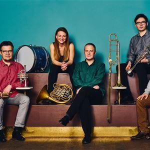 © Miki Anagrius, Gruppen sitter på en röd soffa med sina instrument i famnen.