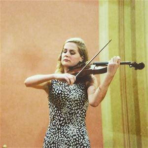 Violinisten håller sin fiol och spelar.