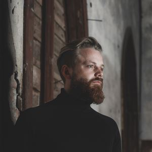 Ulrika Lundholm Ericsson, Pontus i svart polotröja mot putsad vägg med trädetaljer.