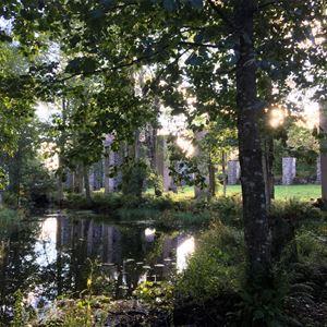 Ett vattendrag med mycket grönska och träd omkring, rester av gammal byggnad skymtar i bakgrunden.
