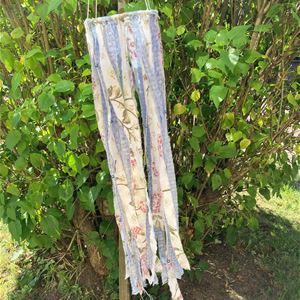 © Karin Jönses, Sommarkrona av tyg som hänger i ett träd.