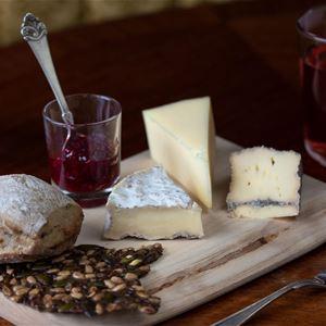 © Eva Grosso, Ett litet träfat med flera olika sorters ostar, med marmelad och bröd.