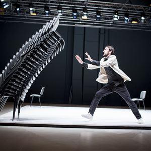© Vojtech Brtnicky, En man på en scen står beredd att fånga en trave med konferensstolar som faller mot honom.