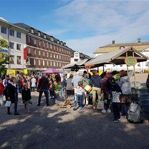 Besökare på en marknad, marknadsstånd, i bakgrunden byggnader.