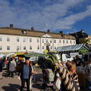 Besökare på en marknad, marknadsstånd, en stor vit byggnad i bakgrunden.