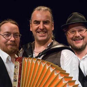 Tre män alla med vit skjorta och svart väst, en håller i ett dragspel och en håller i en ståbas.