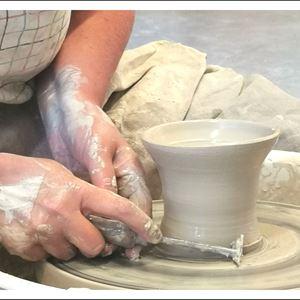 En mugg tar form på en drejskiva, händer och ett verktyg som formar muggen.