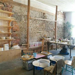 En lokal med stenvägg och träinredning, ett antal drejskivor, stolar, utrustning.
