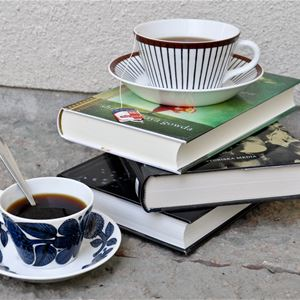 En vit kopp med blommönster, koppen är fylld med kaffe, en sked sticker upp ur koppen, brevid ligger tre böcker ovanpå varandra, överst en kopp fylld med the.