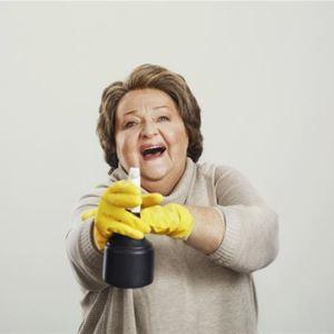 © John Gripenholm, En leende kvinna som har gula plasthandskar på händerna och håller i en sprayflaska.