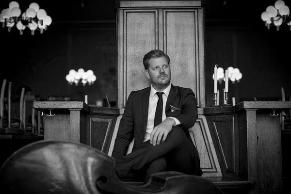 © Privat, En svartvit bild på en man i mörk kostym och slips som sitter med korslagda ben.