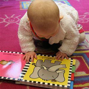 Ett litet barn i vit kofta tittar i en bok.