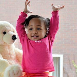 En liten flicka i rosa tröja som sträcker upp armarna, brevid henne en vit stor mjukisbjörn.
