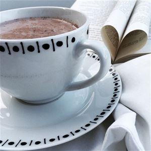 En vit kopp på fat med en slinga med ett svart mönster, en vit servett och en uppslagen bok brevid.