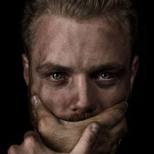 Ansiktet på en man som håller händerna för munnen.