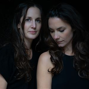 © Anna-Reet Gillblad, En svartvit bild på två kvinnor, båda har en svart topp och långt mörkt hår.