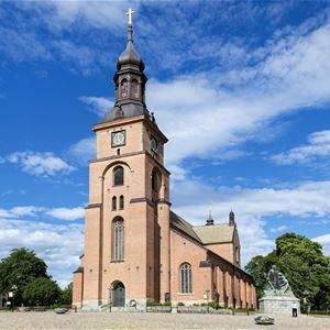 © Ulf Palm, Kristine kyrka, en ståtlig tegelhyrka med två sidoskepp, framför kyrkan et torg med en staty av Engelbrekt.