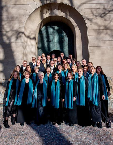 © Elias Gammelgård, En grupp människor iklädda mörka kläder och blåa sjalar, står utanför ingången till en kyrka.