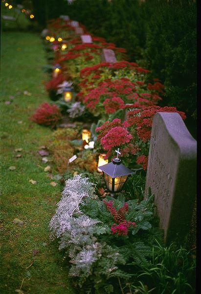 © Jim Elfström/IKON, En kyrkogård på hösten, höstblommor, tända lyktor och gravljus.