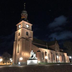 Falu Kristine kyrka på kvällen, upplyst av flertalet lampor, på torget framför kyrkan en staty av Engelbrekt.