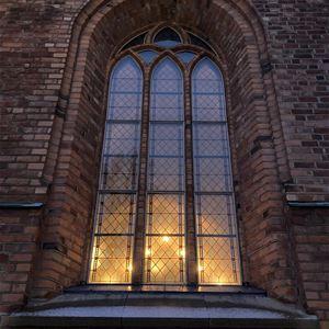 © Anna Kjellin, Ett stort fönster i en tegelbyggnad, det lyser inifrån byggnaden.