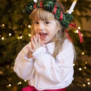 © Kristin Lidell/IKON, En liten flicka iklädd lucialinne och krona, händerna knäppta framför sig, ljulgran i bakgrunden.