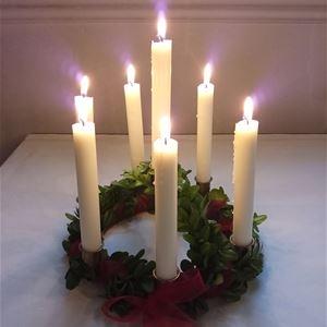© Anna kjellin, En luciakrona med lingonris och tända levande ljus ligger på ett bord.