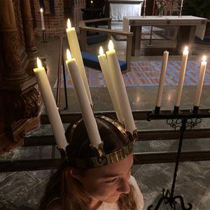 © Anna Kjellin, En flicka i luciakrona, brevid henne en ljusstage på fot med fyra ljus.