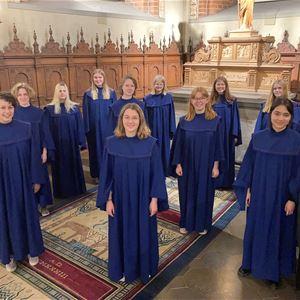 © Anna Kjellin, Kvinnor i blåa körkåpor som står inne i en kyrka.