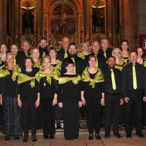 En grupp människor i svarta kläder, kvinnorna har gröna sjalar och männen har gröna slipsar.