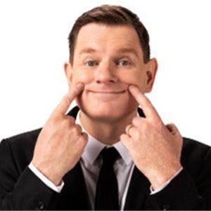 Al Pitcher i svart kavaj, vit skjorta och svart slips håller upp sina mungipor med pekfingrarna.