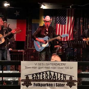 Ett band som spelar på en scen, 3 män med gitarr, en som spelar keyboard, flaggor i bakgrunden, skylt Säterdalen i framkant.